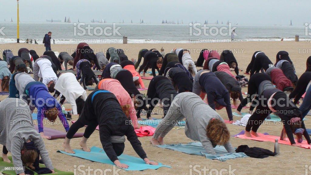 Veel mensen die Yoga oefening voor gezondheid en ontspanning op het strand - Royalty-free Afdalen Stockfoto