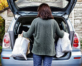 A woman filling up the boot of the car with shopping bags