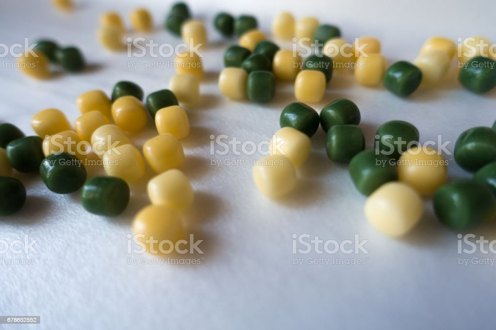 Lots of small yellow and green candy drops stock photo