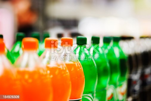 A long line of unbranded soda bottles in various flavours and colors, the focus on the center of the line.