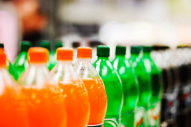 lots of soda bottles in various flavours all lined up - soda pop stock photos and pictures