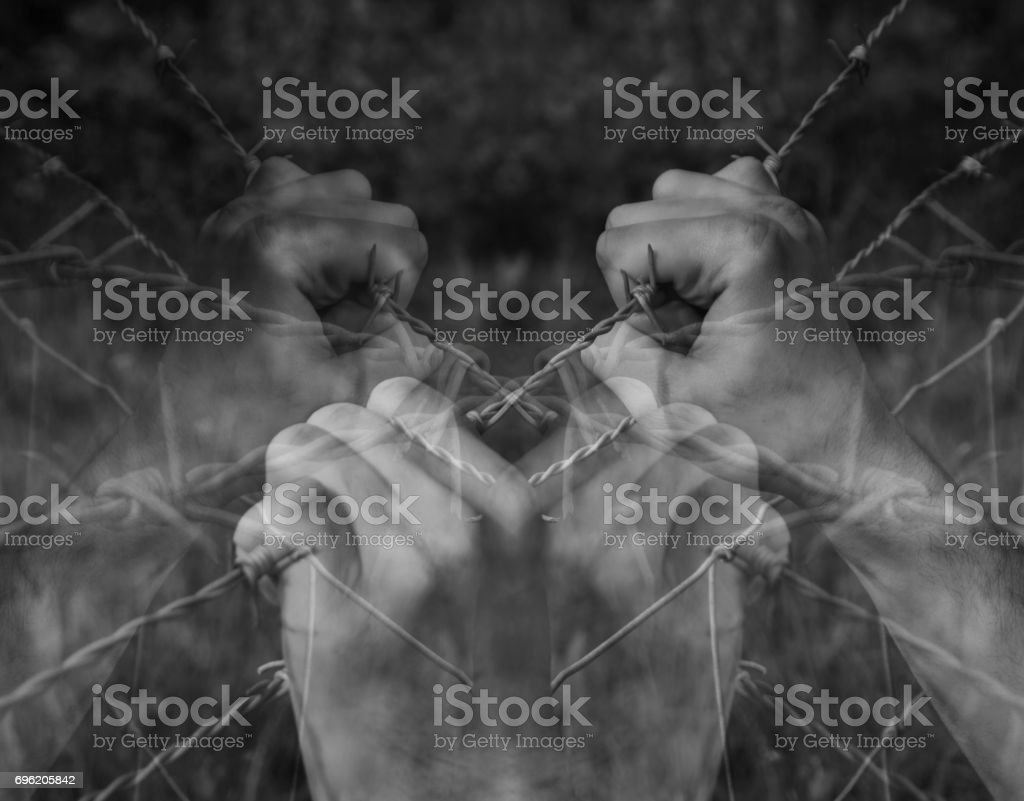 Lots of tortured hands grasping desperately barbed wire on black and white background stock photo