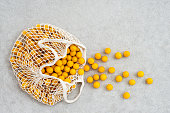 istock Lots of yellow plums in a mesh shopping bag 1039128820