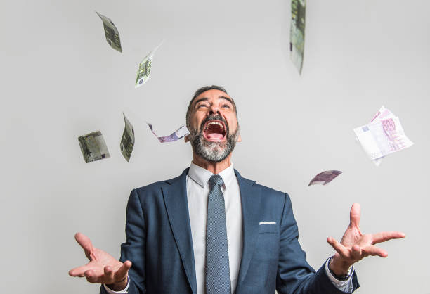 Lottery and money win Excited senior business man throwing money, euro bills, in the air, celebrating victory and success lottery stock pictures, royalty-free photos & images