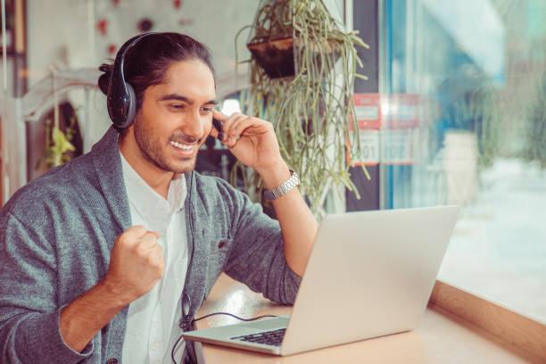 lottery winner. man smiling having a online conversation looking at laptop screen, cheering, pumping fist at laptop - call center стоковые фото и изображения