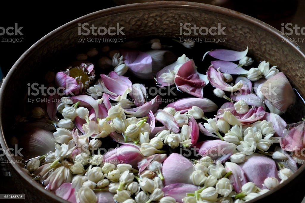 Lotus petals and jasmine flowers in bowl of water stock photo