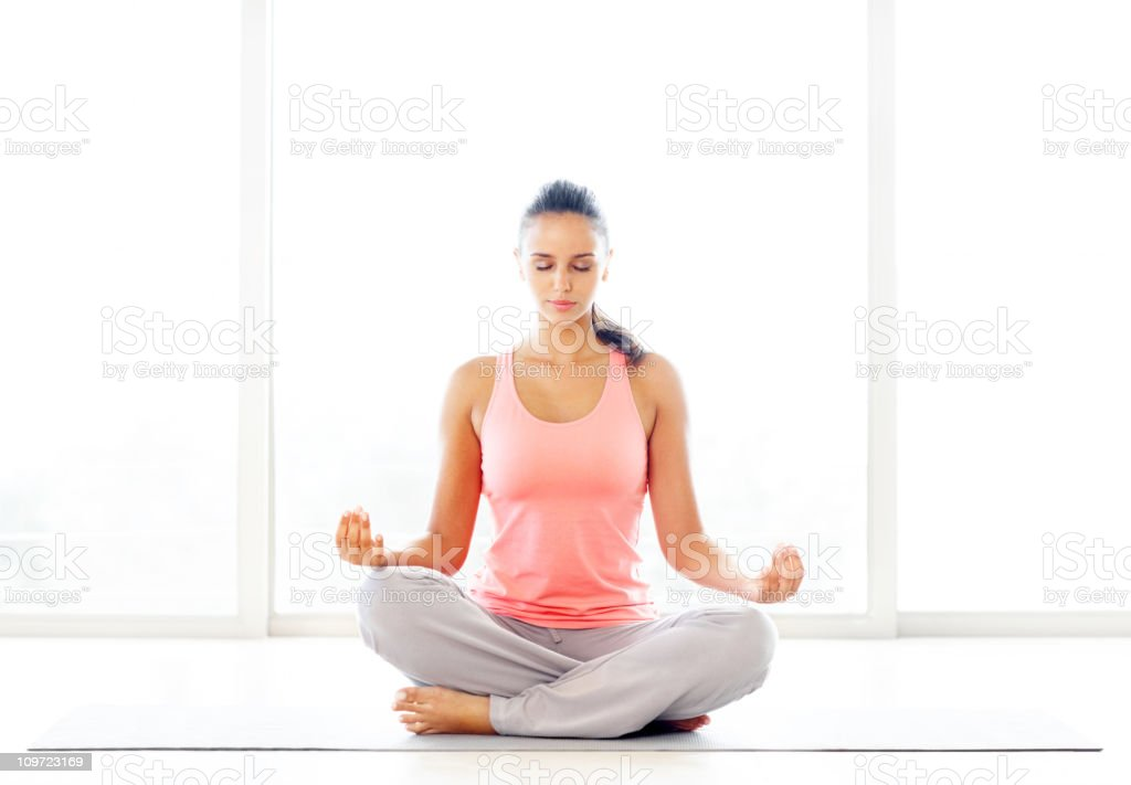 Lotus position - Young casual woman practicing yoga royalty-free stock photo