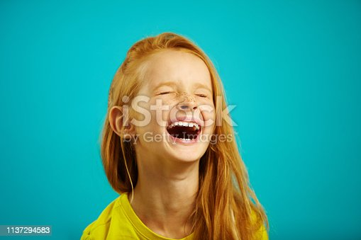 Loud and strong laughter of little girl with red hair, wearing yellow t-shirt, a shot of child on blue background.