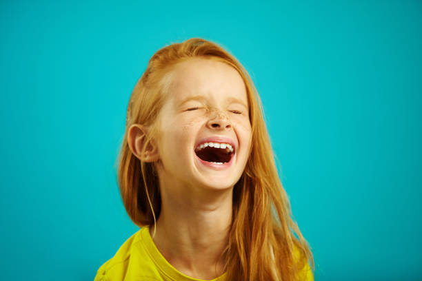 loud and strong laughter of little girl with red hair, wearing yellow t-shirt, a shot of child on isolated blue. - ridere foto e immagini stock