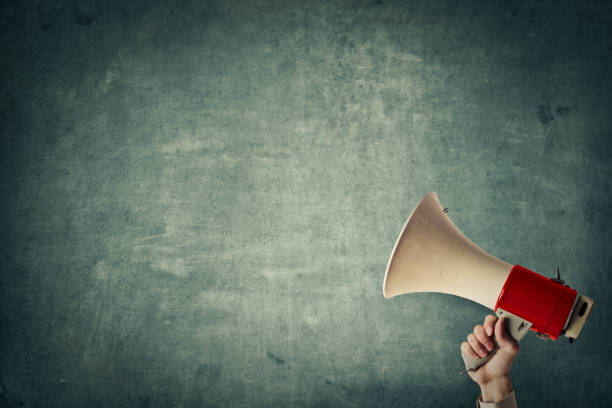 Loudspeaker Megaphone in front of a blue wall information sign stock pictures, royalty-free photos & images