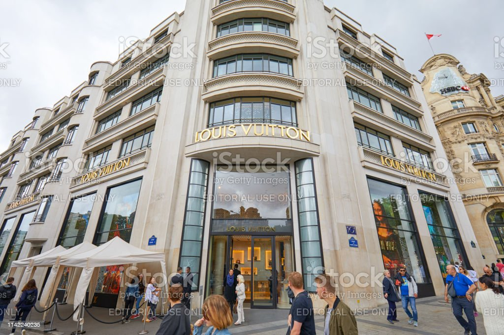 Louis Vuitton fashion luxury store in Champs Elysees, people passing...