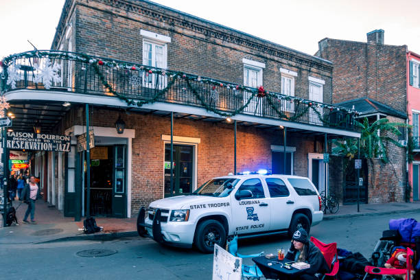 Louisiana State Trooper or Police vehicle in front of a jazz bar New Orleans, USA - Dec 4, 2017: Louisiana State Trooper or Police vehicle in front of a jazz bar. A lady palm and tarot card reader on the sidewalk along Bourbon Street in the iconic French Quarter. trooper stock pictures, royalty-free photos & images