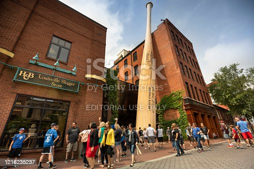 Louisville, Kentucky - June 22, 2019:  People gather on the sidewalk outside of the Louisville Slugger museum and factory.  Resting on the exterior building is the world's largest baseball bat