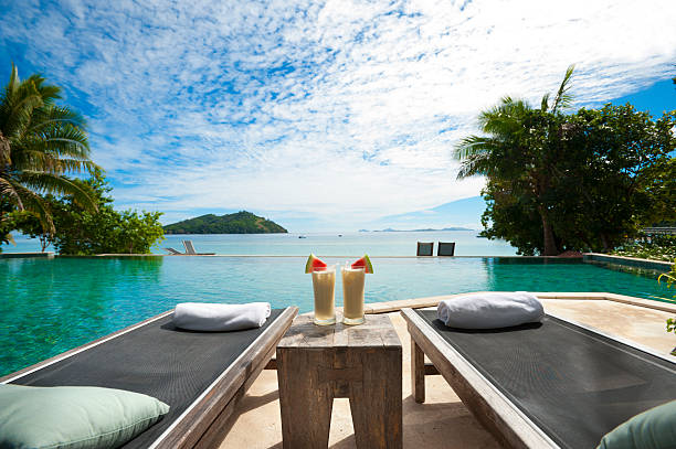 a lounge beside the pool with cocktails on table - hawaii home stock photos and pictures