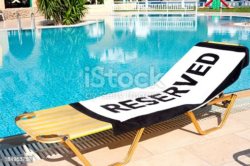 A beach towel with the word 'Reserved' spread onto a sun lounger beside a swimming pool