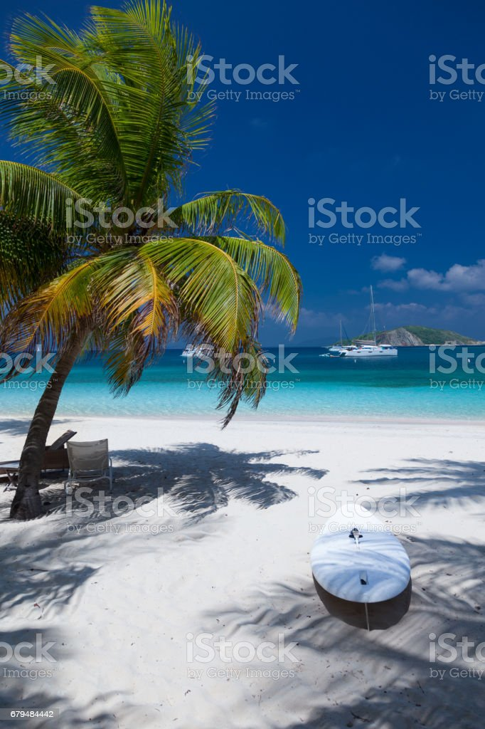 lounge chair under palm tree on beautiful tropical beach royalty-free stock photo