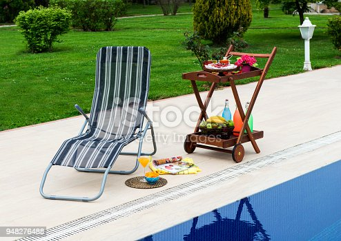 Lounge chair with serving trolley on wheels for dining or drinks in garden.