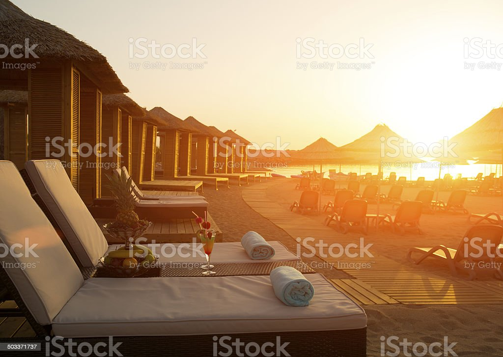 Lounge chair with sunset stock photo