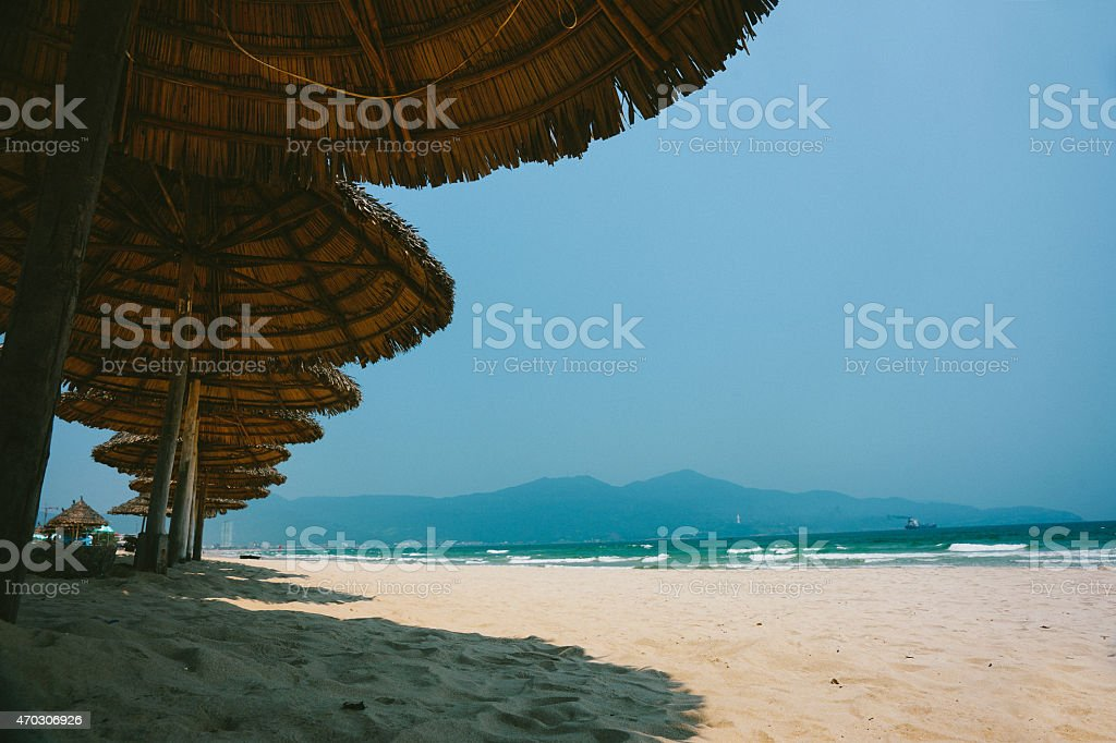 Lounge Chairs and Grass Umbrella at the Beach stock photo