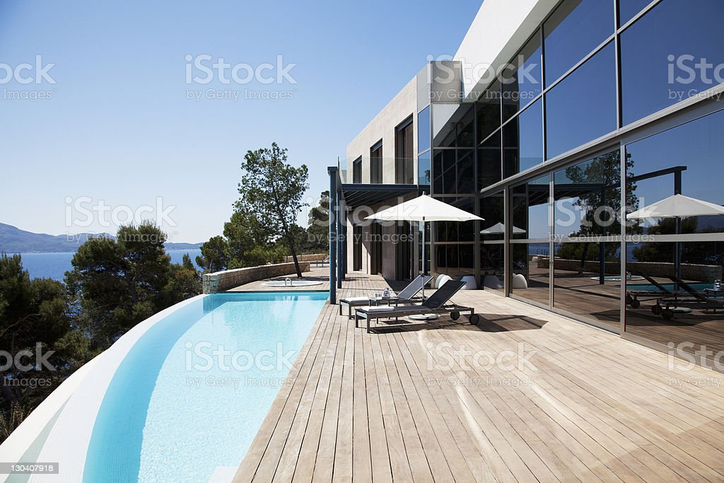 Lounge chairs and pool outside modern house stock photo