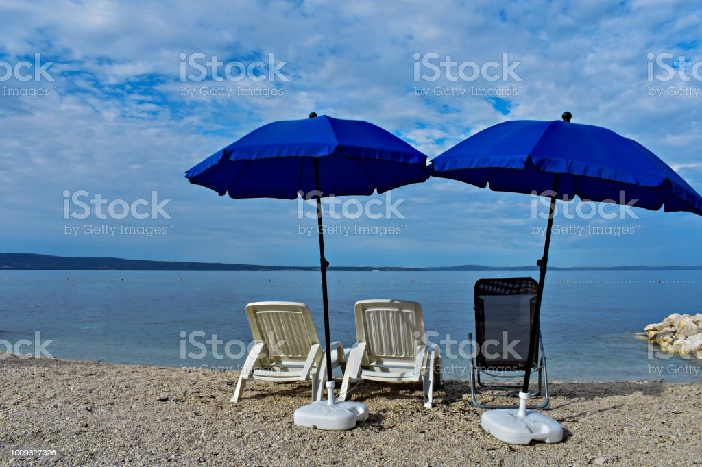 Outdoor Natural Gas Fire Pit Table, Lounge Chairs And Sun Umbrellas At The Beach With Cloudy Blue Sky And Sun Stock Photo Download Image Now Istock