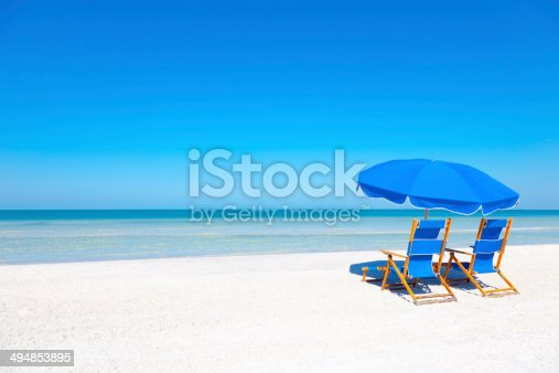 Two blue beach loungers and umbrella at white sandy beach