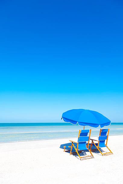 Sedie a sdraio e ombrellone sulla spiaggia - foto stock