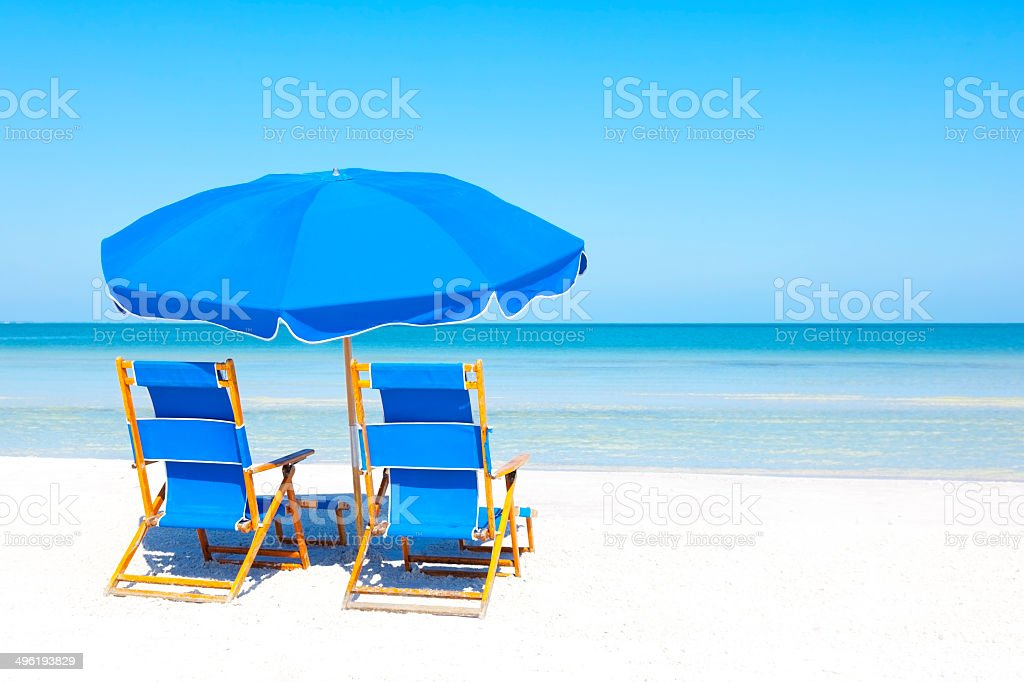 Lounge Chairs And Umbrella At The Beach Royalty Free Stock Photo