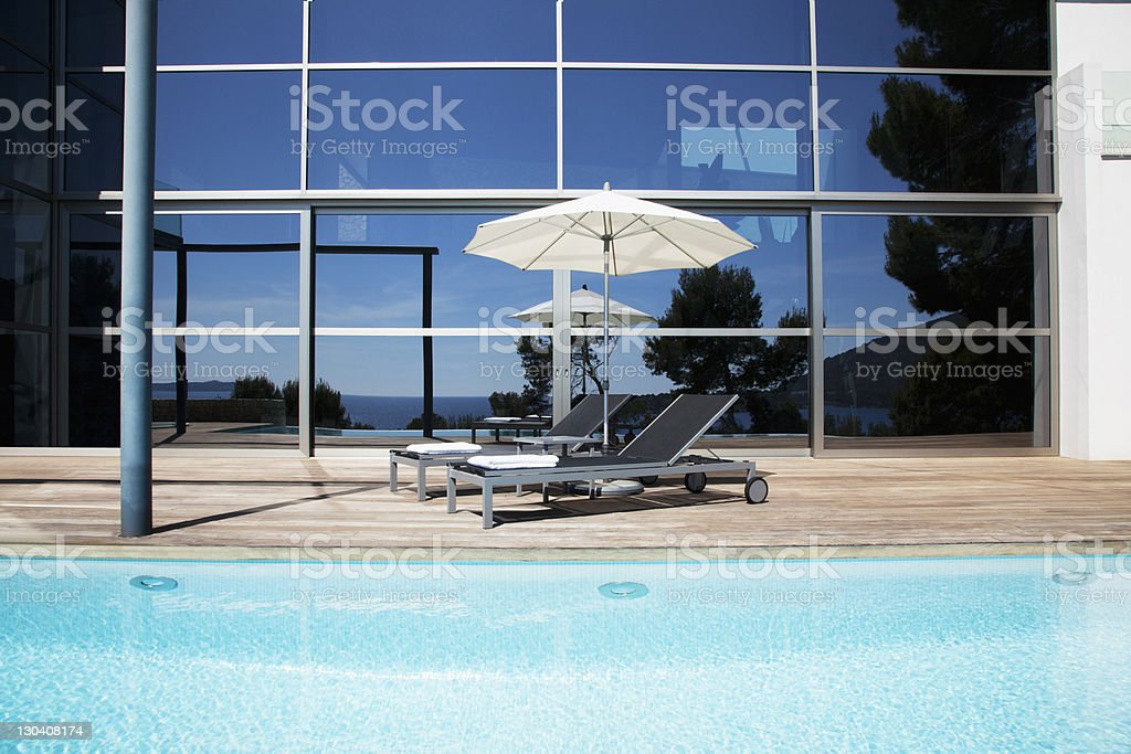 Lounge chairs and umbrella beside pool royalty-free stock photo