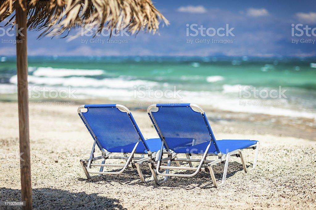 Liegestühle und Sonnenschirm am Strand – Foto