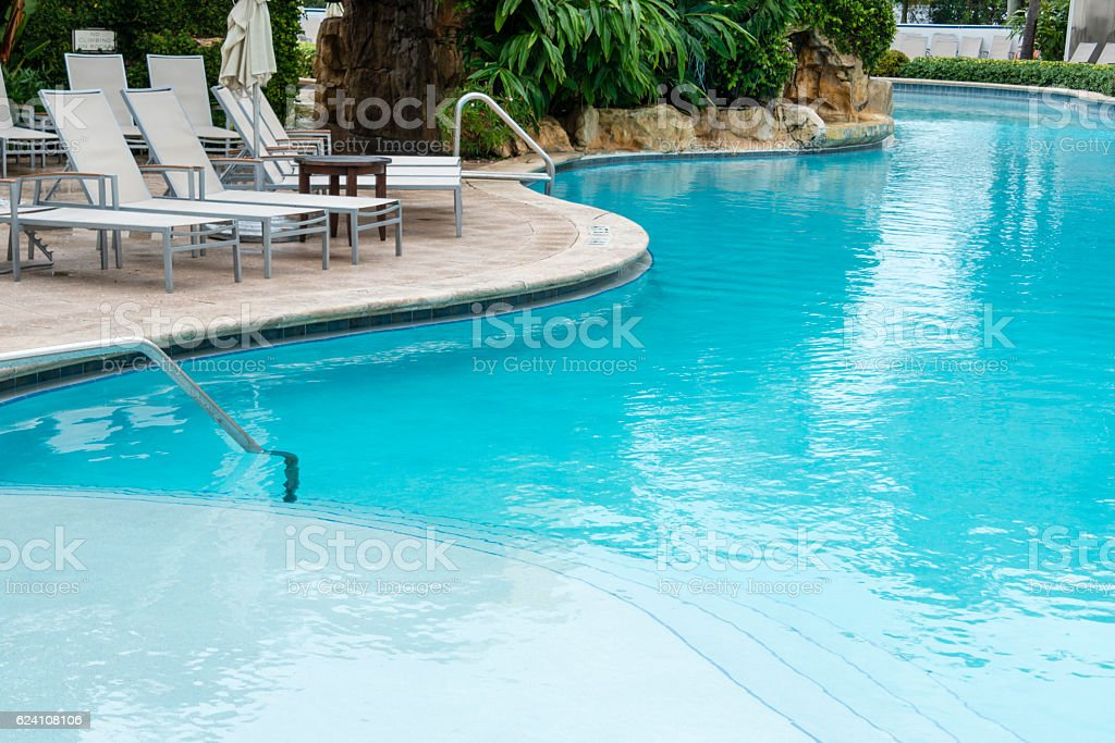 Lounge chairs next to swimming pool with curved steps. stock photo