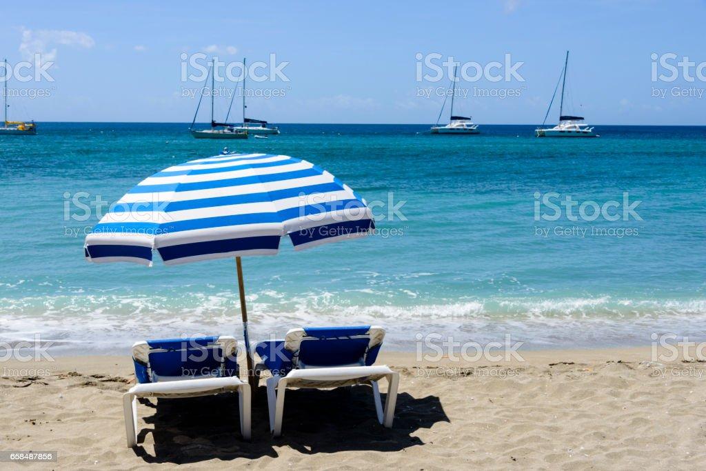 Sonnenliegen Unter Einem Sonnenschirm Am Strand Stockfoto