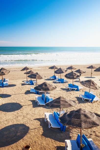 liegestühle mit sonnenschirm am sandstrand - urlaub in tunesien stock-fotos und bilder