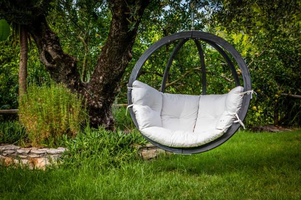lounge hangende stoel met wit kussen in de tuin met groene natuur achtergrond - schommelen bungelen stockfoto's en -beelden