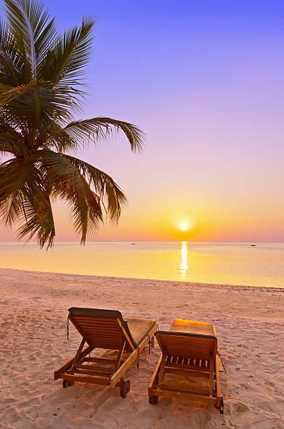 Loungers on Maldives beach stock photo