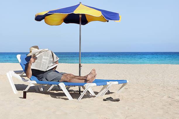 lounging - newspaper beach stockfoto's en -beelden