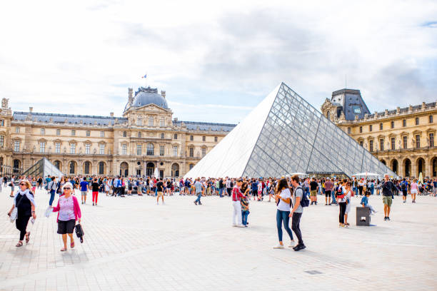 Louvre museum in Paris PARIS, FRANCE - August 02, 2017: View on the Louvre museum square full of people during the cloudy weather. Louvre is the world's largest museum and a historic monument in Paris musee du louvre stock pictures, royalty-free photos & images