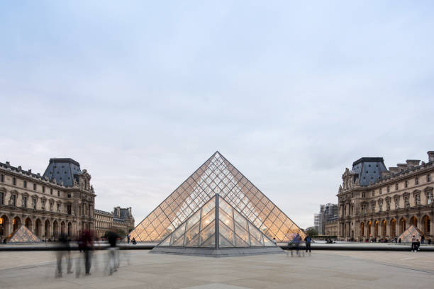 Louvre Museum, Paris, France Paris, France - September 10, 2017 : Long exposure of people walk along the Louvre Museum in the evening. musee du louvre stock pictures, royalty-free photos & images
