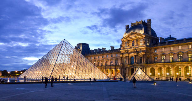 Louvre Museum The Louvre is one of the most famous monuments and tourist attractions in Paris. This photo was taken during a warm spring evening after sunset in the museum courtyard and features the grandoise architecture of the palace. It also shows some of the manny visitors that this world class destination receives every day. musee du louvre stock pictures, royalty-free photos & images