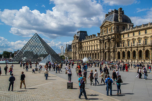 Louvre Museum tourist Paris, France - August 15, 2014: Beautiful picture of the Louvre Museum located in Paris, France. The picture shows the pyramid entrance and the main building at the right side. Some people walking around and taking photos can also be seen in the picture. musee du louvre stock pictures, royalty-free photos & images