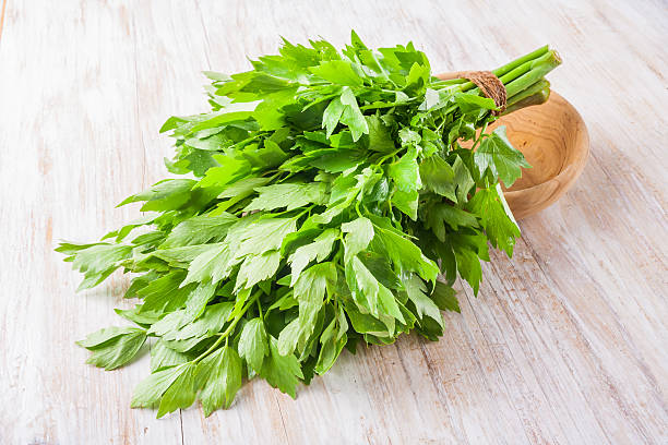 lovage leaves on a wooden table stock photo