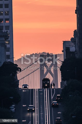 A couple holding hands while getting on a trolley on California Street in San Francisco at sunrise. Bay Bridge in the background.