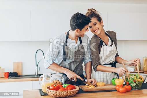 Lovely couple making salad in the kitchen.