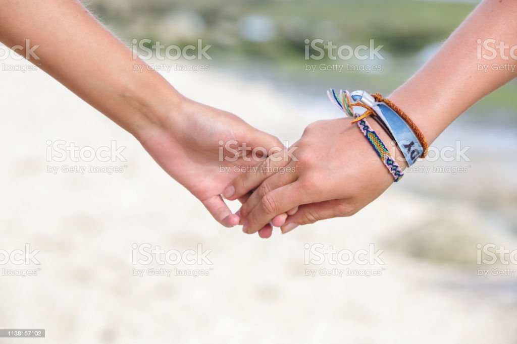 Love and friendships concept. Holding hands closeup, outdoor candid...
