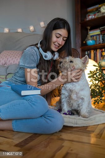 Teenage girl reading a book and have a fun with her cute white dog