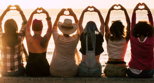 Love and meditation lifestyle concept - group of women looking at the sunset on the ocean and make the hearth with hands - romantic golden light and valentine's day concept - friendship forever stock photo
