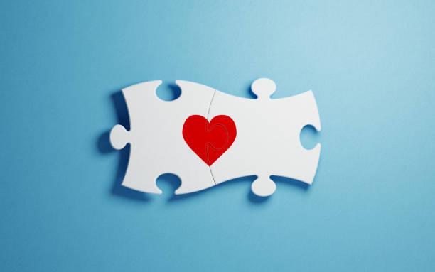 love and puzzle concept - white jigsaw puzzle pieces forming a red heart - romanticismo concetto foto e immagini stock