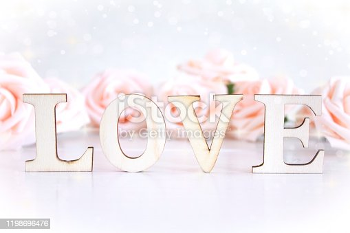 The word Love with pale pink roses in the background, bokeh lighting and copyspace.