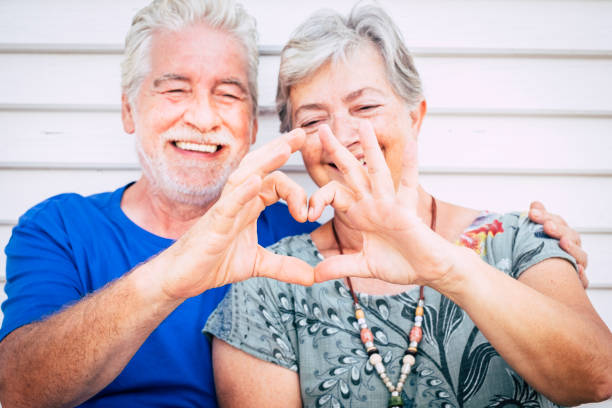 love and valentine's day concept for cheerful happy couple of senior man and woman caucasian people together doing hearth with hands and smile - happiness after life together forever - senior valentine stock photos and pictures