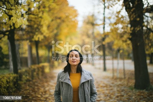 Beautiful Girl with hat standing outdoor with closed eyes and hands in pocket